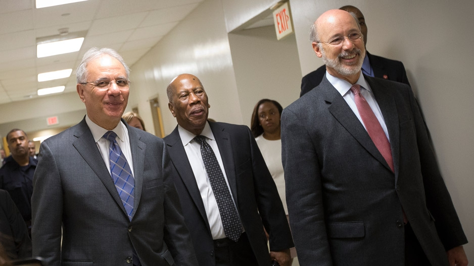Three men in suits touring the new medical suite at Temple's dental school.