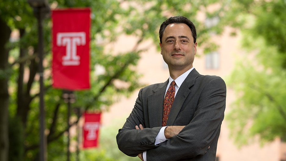 Gregory N. Mandel standing by a Temple flag.