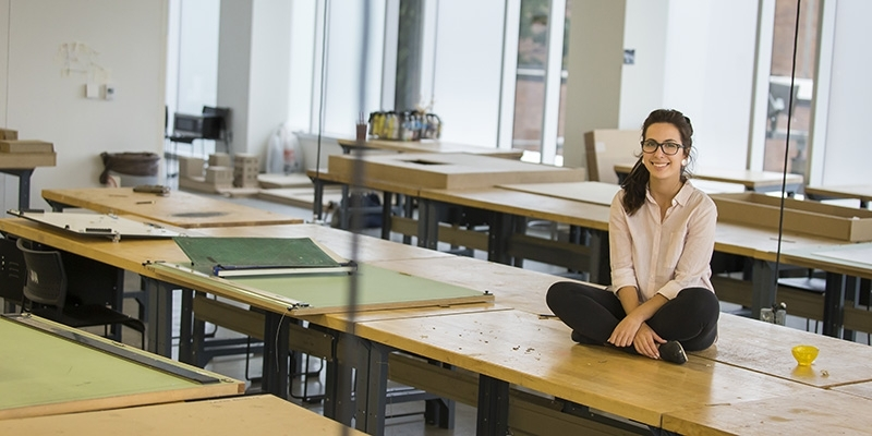 Maryam Hallaj sitting on a studio table in the architecture building.