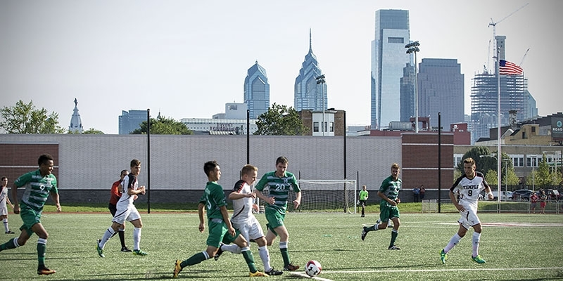 Temple men's soccer team playing at the new sports complex with the Philadelphia skyline in the background.