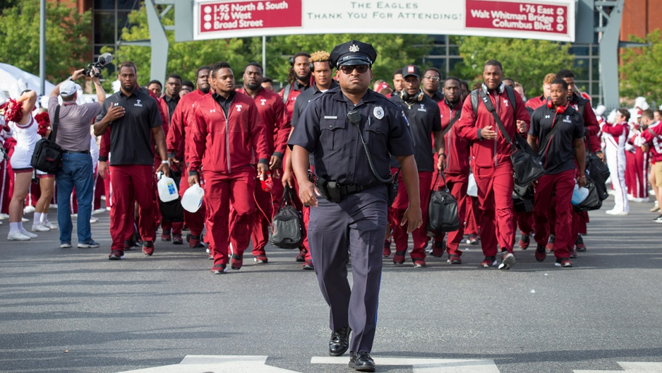 a Temple University police officer escorting football players as they walk into Lincoln Financial Field.