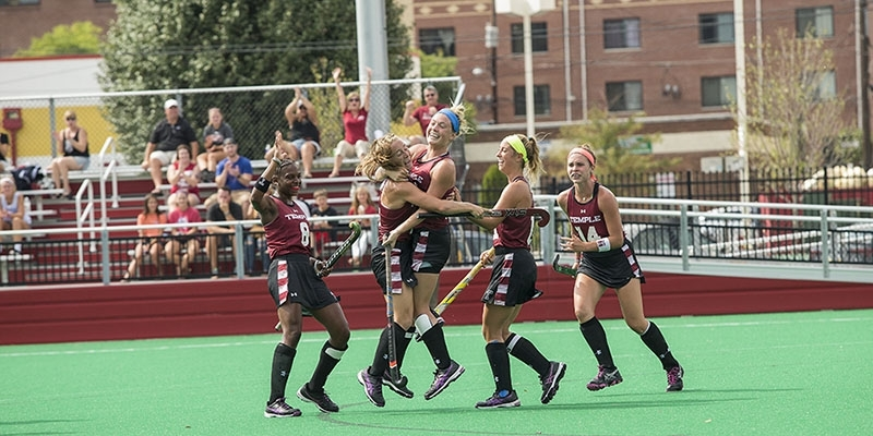 Temple's field hockey team celebrating on the field.