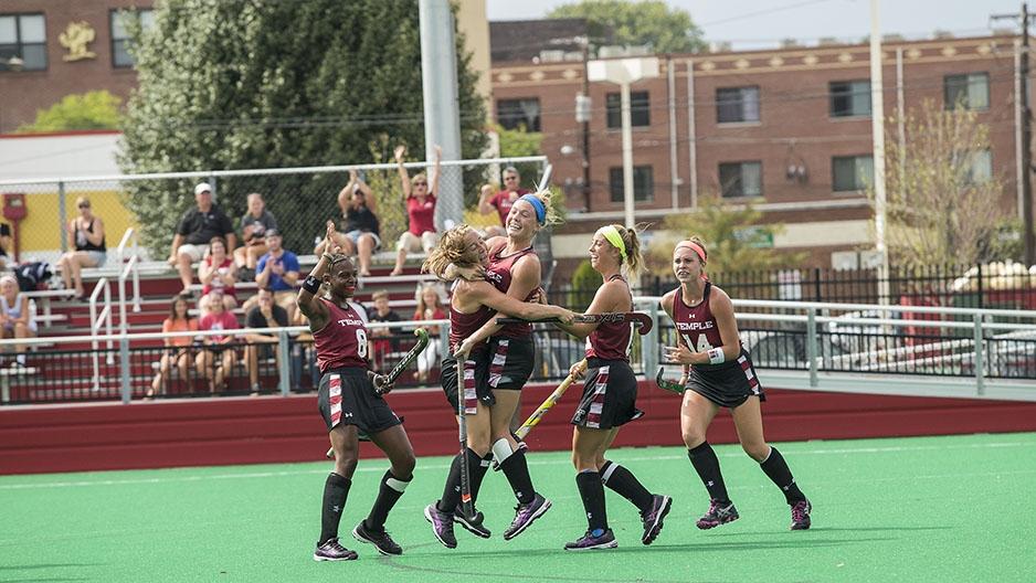 Temple's field hockey team celebrating on the field.