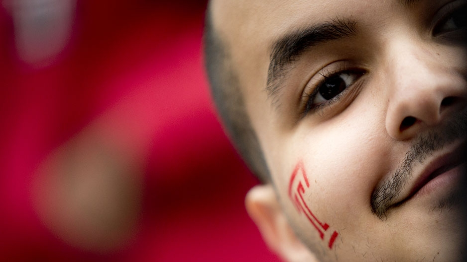 "A close up of a man with a red Temple ""T"" painted on his face."
