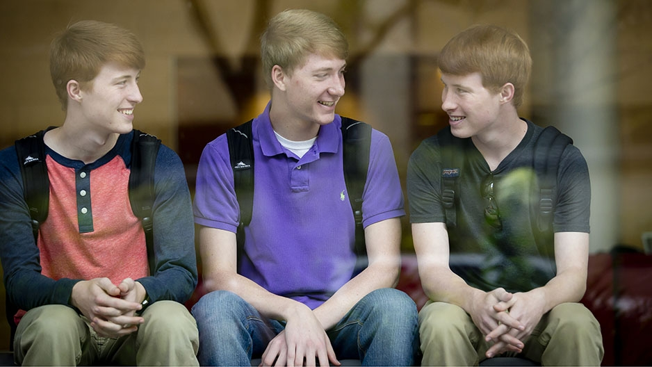 Three young men sitting and talking together.