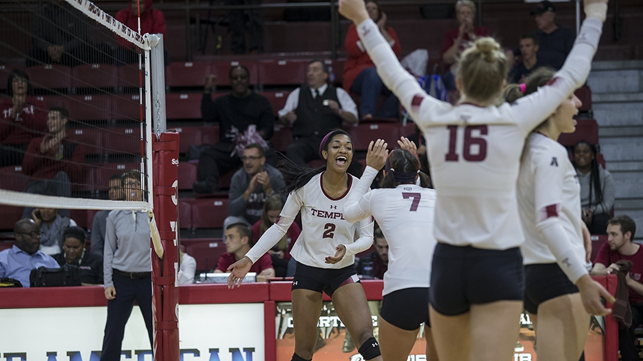 Temple's volleyball team cheering on the court.