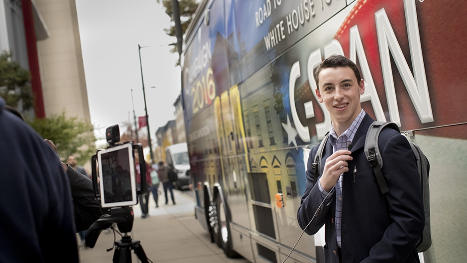 A student standing in front of the C-SPAN Bus along 13th Street.