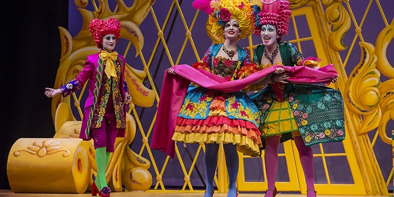 Three opera singers wearing brightly colored costumes and wigs performing on stage.