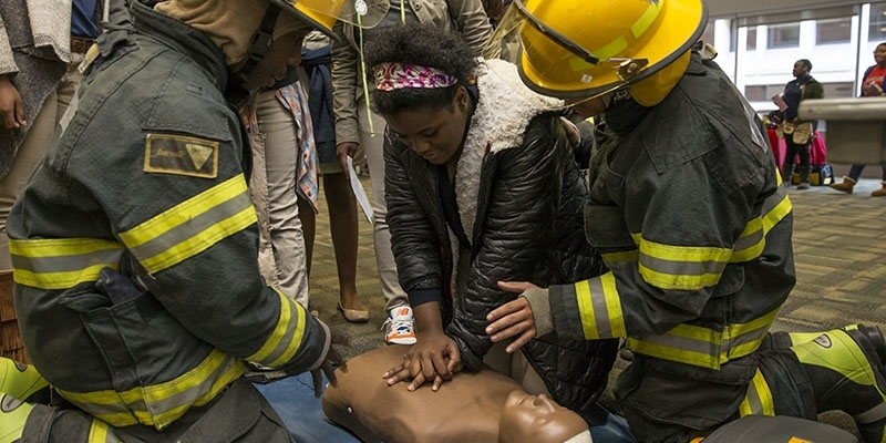 two firefighters teaching a female student how to perform CPR.