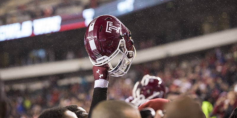 A Temple football helmet held high above a crowd of football players.