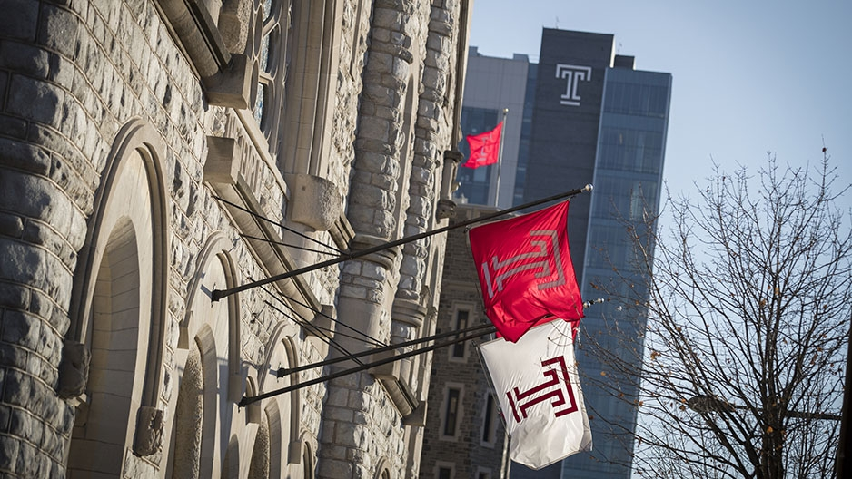 Temple flags hanging from the Temple Performing Arts Center with Morgan Hall in the background.