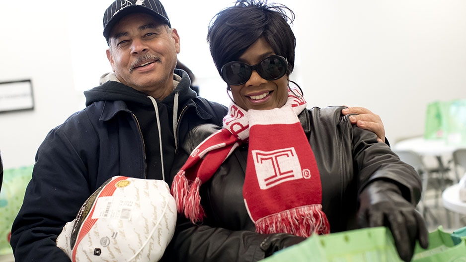 a man and a woman smiling and holding a frozen turkey.