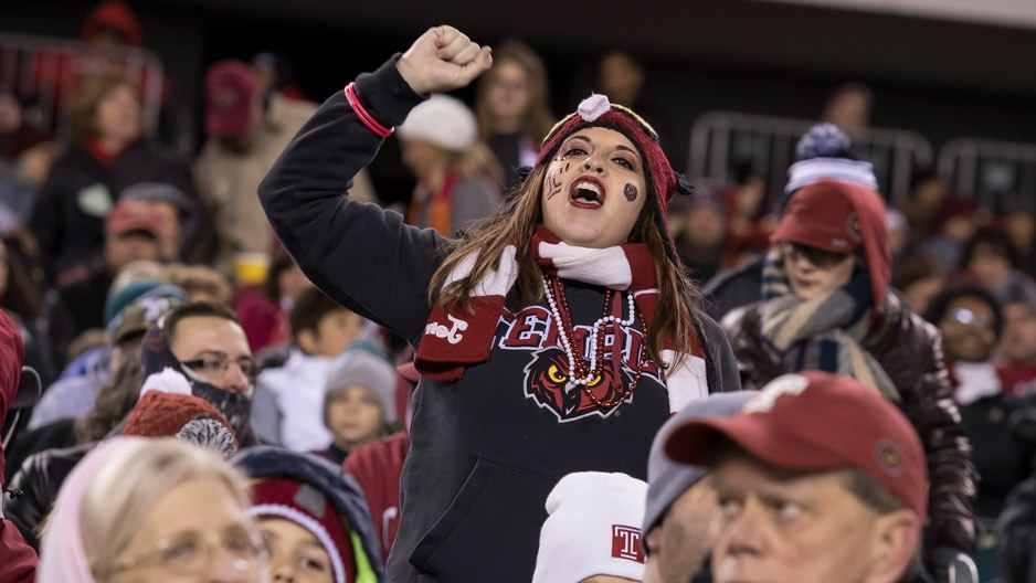 a fan in the crowd wearing Temple gear, cheering on the Temple football team.
