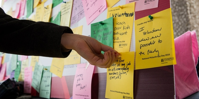 a student posting a note about giving back on a board for National Philanthropy Day.