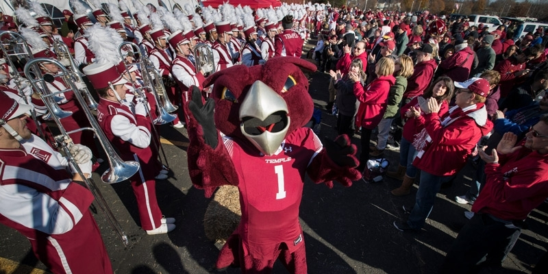 Temple mascot Hooter the Owl celebrating with the marching band and fans.