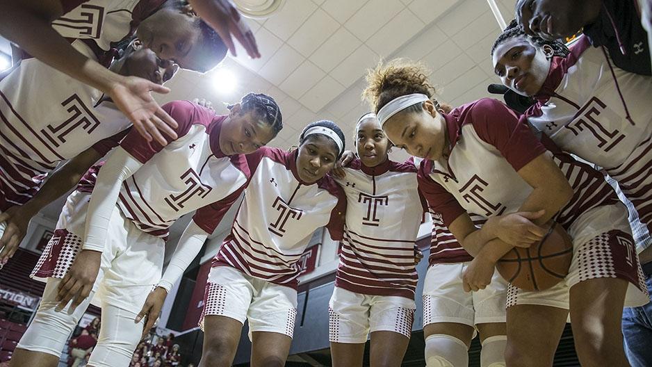 The women's basketball team having a team huddle.