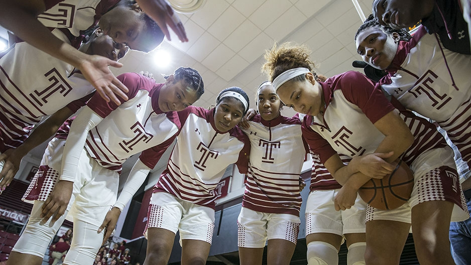 The women's basketball team having a team huddle.