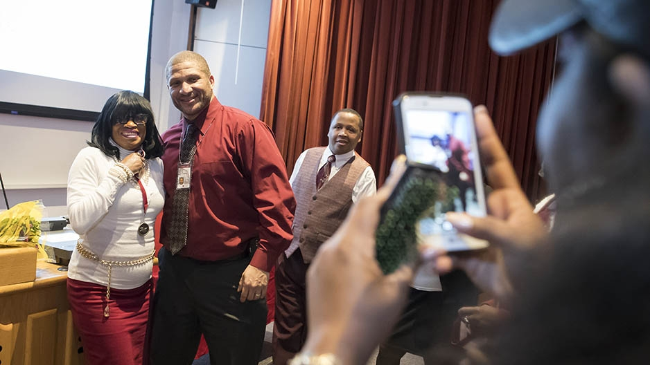 A student and an administrator getting their picture taken with a cell phone.