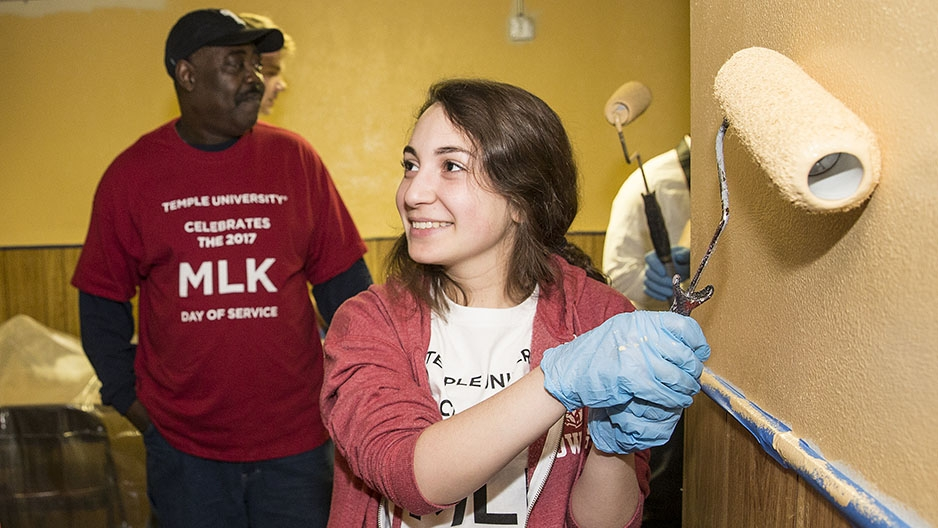 A student painting a wall as part of a service project.