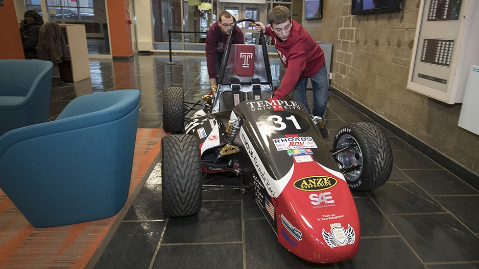 Two students pushing the race car through the engineering building.