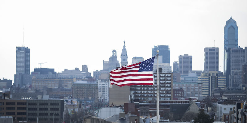 The US flag flying against the Philadelphia skyline.