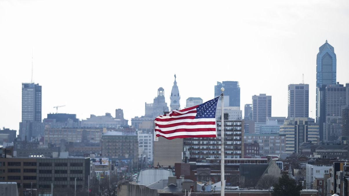 The US flag flying against the Philadelphia skyline.