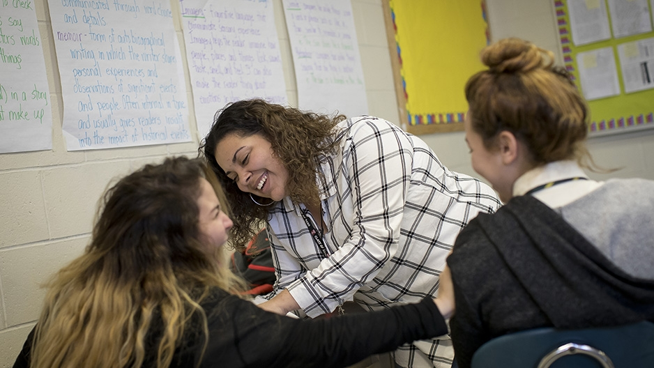 A female Temple student interacting with high school students in a classroom.