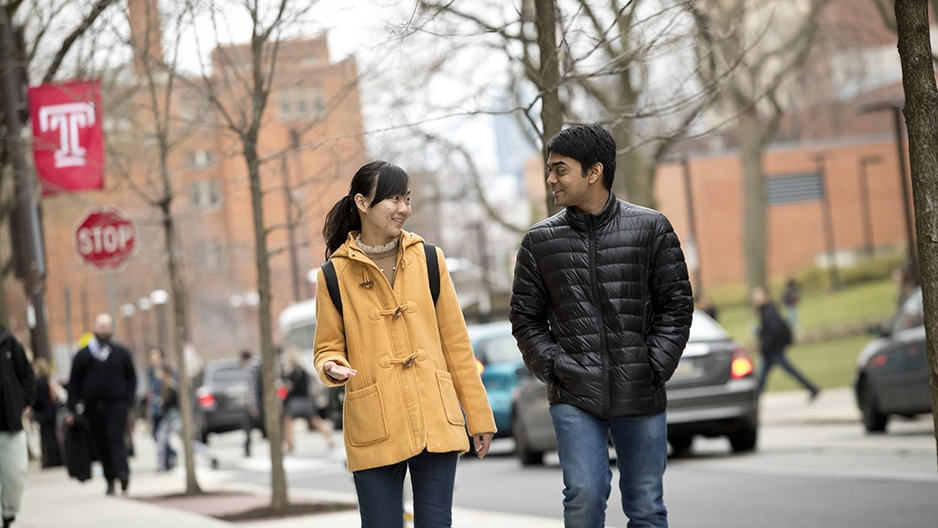 Two students talking to each other as they walk north on 12th Street on campus.