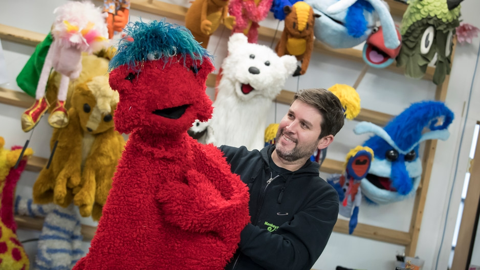 Michael Latini holding a furry red puppet.