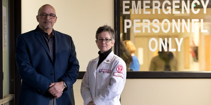 Surgeon Amy Goldberg and outreach coordinator Scott Charles standing by ER doors