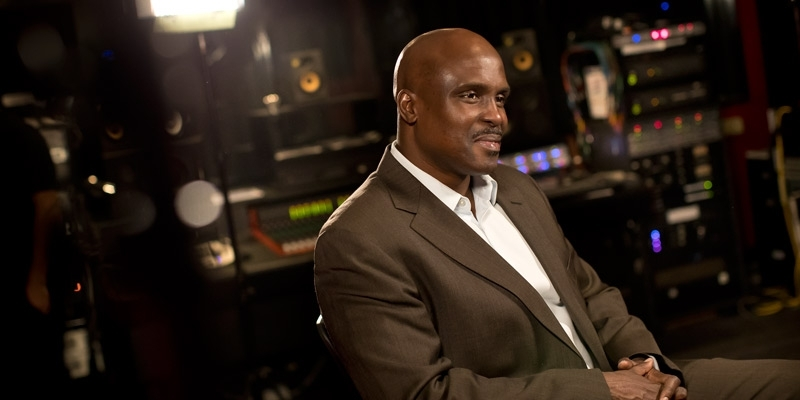 A man in a brown suit sitting in a recording studio.
