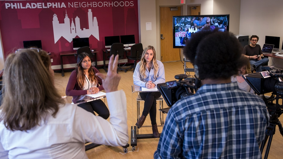 students sitting at an anchor desk and running cameras on a temporary TV set
