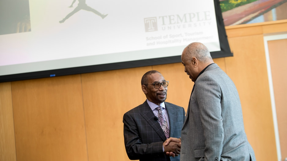 Larry Miller shaking hands with Temple's Jeffery Montague
