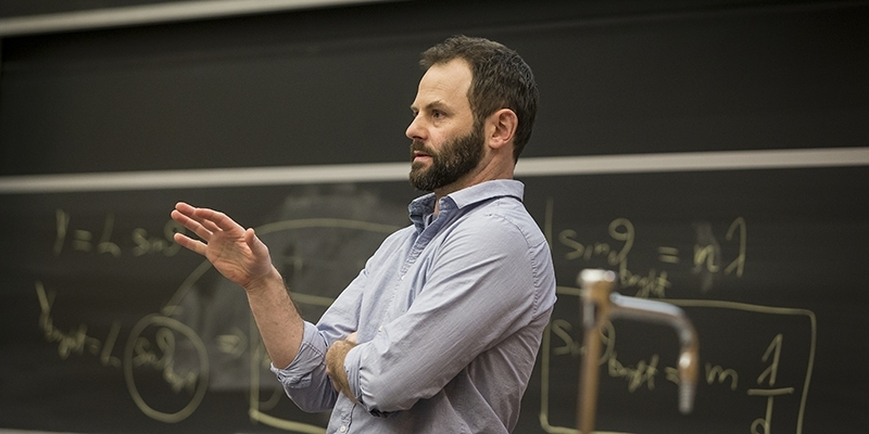 Erik Cordes leading a lecture in front of a chalkboard.