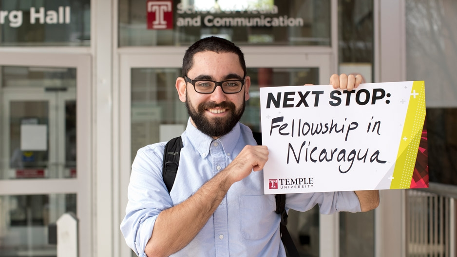"""Eli LaBan holding up a sign that says """"Fellowship in Nicaragua."""""""