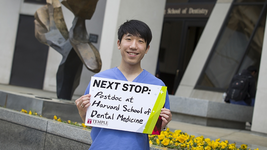 "Andy Lee holding a sign that says ""Next stop: postdoc at Harvard School of Dental Medicine."""