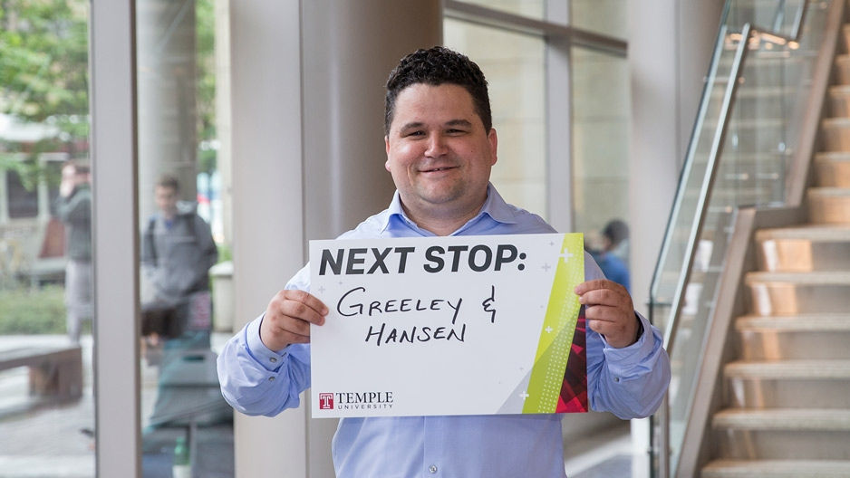 A man in a blue shirt holding a sign that reads Next Stop: Greeley and Hansen.
