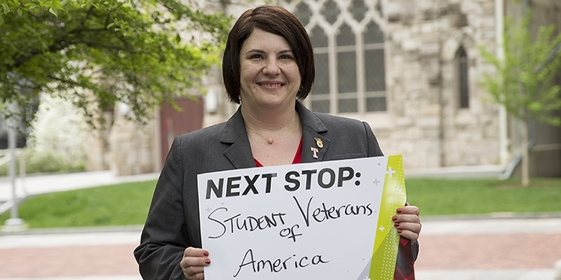 "Tammy Barlet holding a sign that says ""Next stop: Student Veterans of America."""