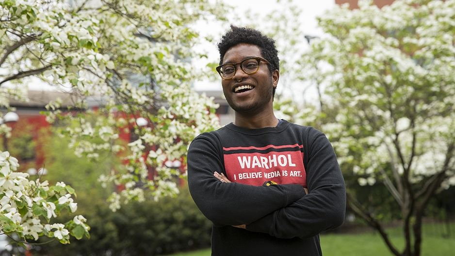 Christopher Persaud standing in front of flowering trees smiling with his arms crossed.