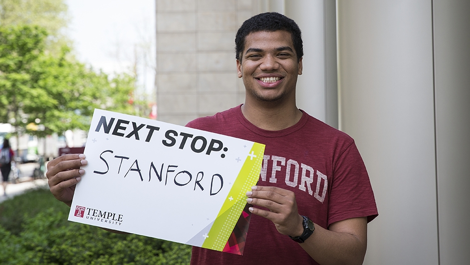 Chey Jones holding a sign for his next stop, Stanford University.
