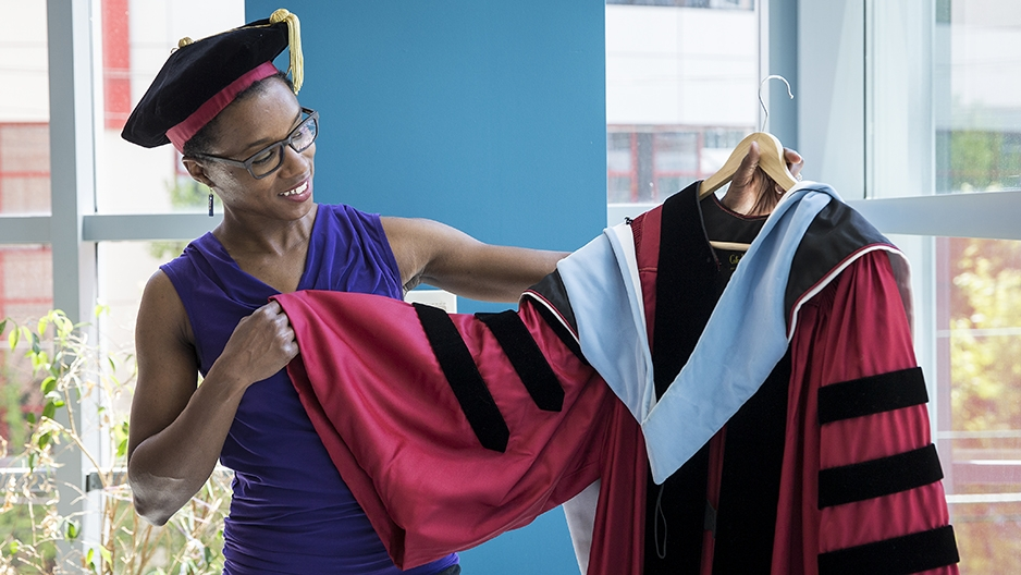 Musu Davis holding and eyeing the cherry graduation gown