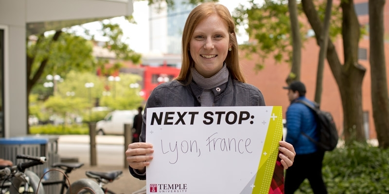 Amelia Schunder holding up a sign that says Next Stop: Lyon, France