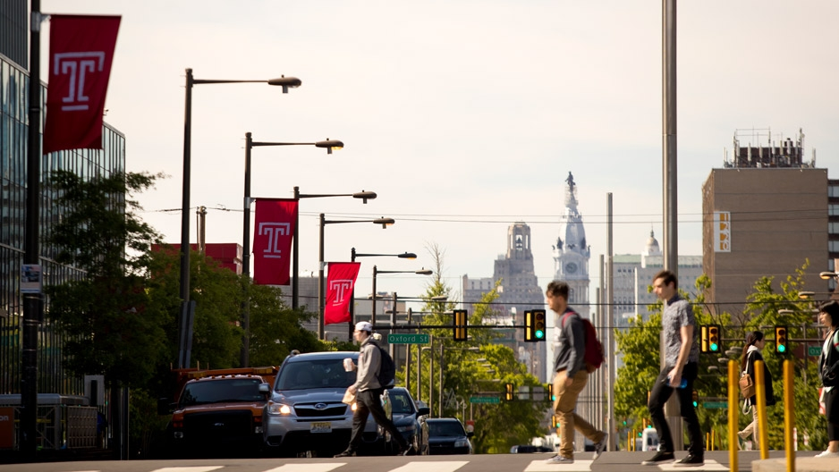 Students crossing Broad Street under red Temple flags.