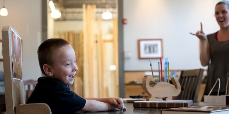 Mark Ovington, 5, sitting in his adaptive chair made of cardboard