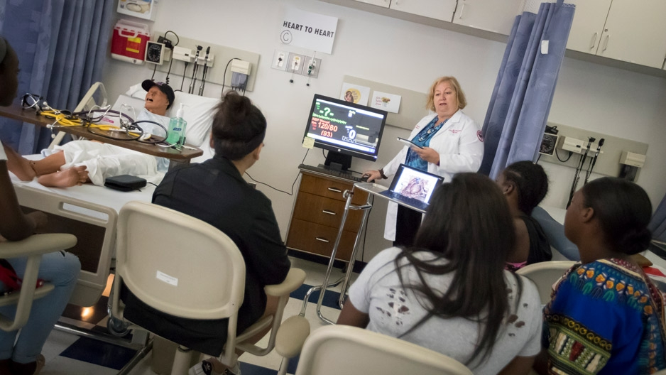 a nurse teaching students in a hospital room