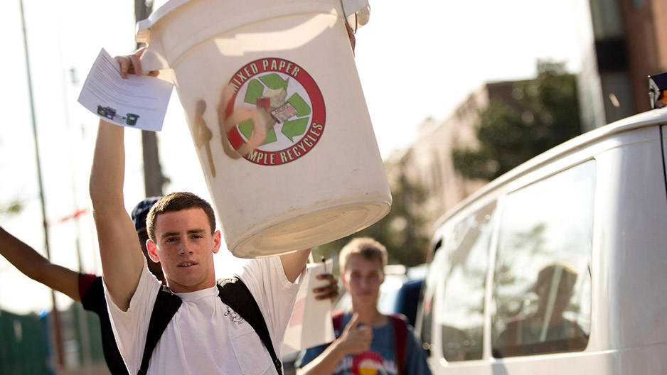a student holding up his recycling bin