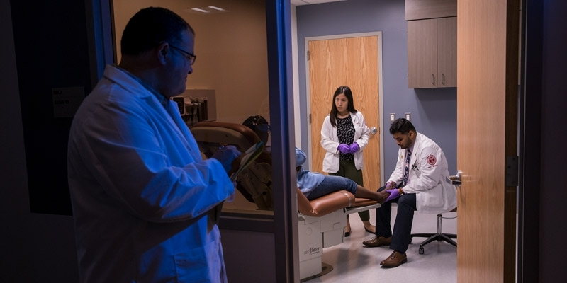 A physician watching two students work with a patient in a clinic room