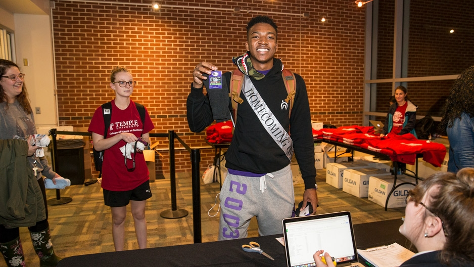 male student wearing a homecoming sash donates socks