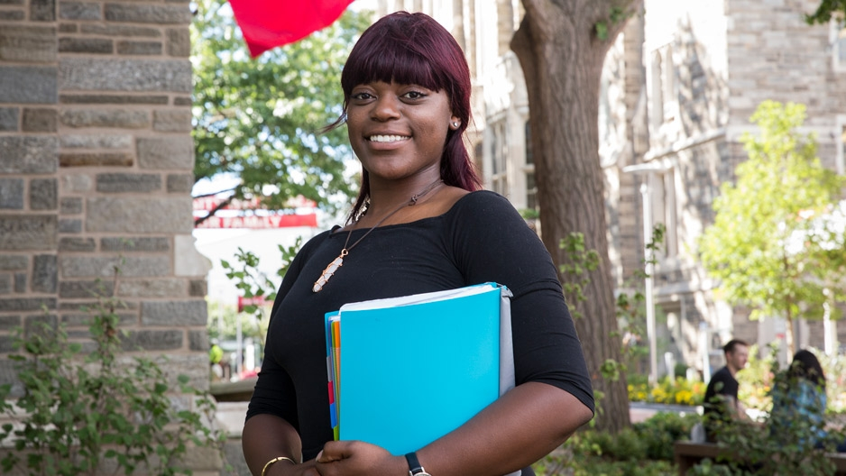 Briana Drummer, a former foster care youth, smiles outside Sullivan Hall at Temple University.