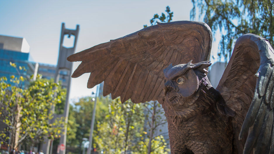 The new owl statue on campus with the Bell Tower in the background